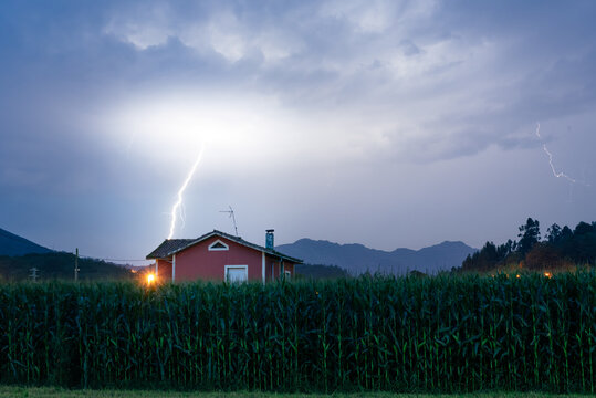 lightning storm over country house at night with mountains in the background.