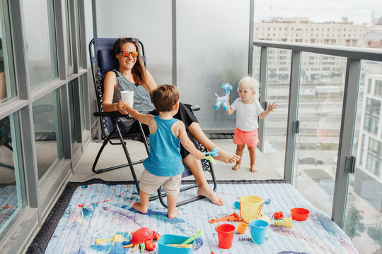Young mother spending time together with children babies on balcony at home. Staycation during coronavirus covid-19 pandemic in world. Preventive measures against virus spread.