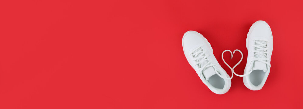 White sports shoes and heart shape from laces on a red background. Simple flat lay with copy space.