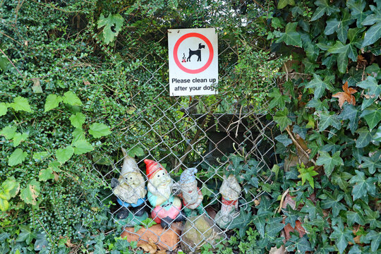Humorous group of garden gnomes and a sign to clean up dog mess seen in a garden in the village of Nether Stowey in Somerset