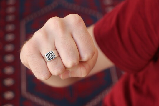 "Man hand with a silver ring on his finger. Ottoman arabic numeral men's ring. ""Abjad"" Islamic Talisman Ring. Arabic numbers (1 to 9) are written on the ring."