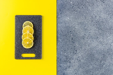 Creative food background of Ultimate Gray and Illuminating trending color. Lemon and cutting board on gray and yellow table surface