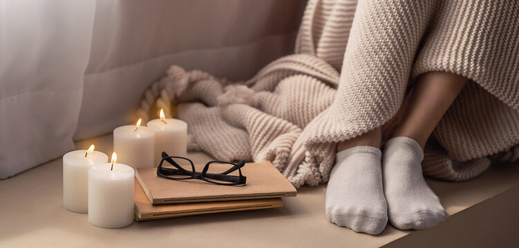 Cup of coffee and candle cozy bed with book and blanket. Warm woolen sweater in cold autumn or winter weekend, Lazy day, Cosy scene, hygge concept banner