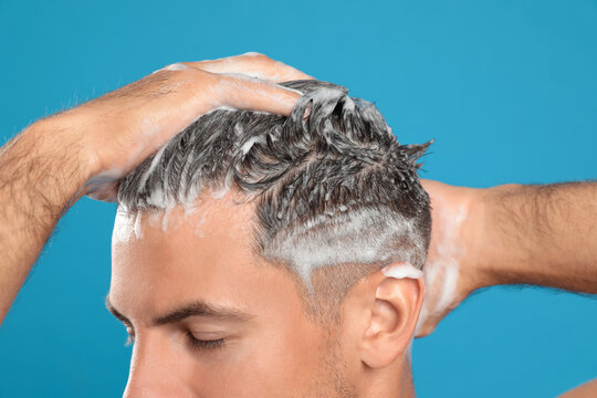 Handsome man washing hair on light blue background, closeup