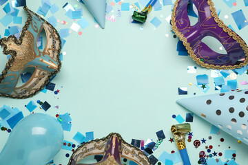 Frame of beautiful carnival masks and party decor on light blue background, flat lay. Space for text