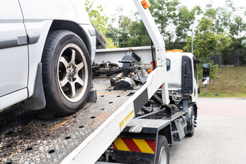 Obraz Cable attached to broken down car being pulled onto tow truck - fototapety do salonu
