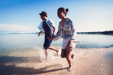 Asian teenage girl and boy running on the beach