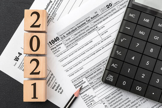 """Pay tax in 2021 year. Wooden cubes with numbers """"2021"""" on tax forms at office workplace. Business concept."""