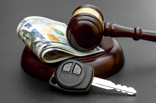 Judge's gavel with car key and money on black.