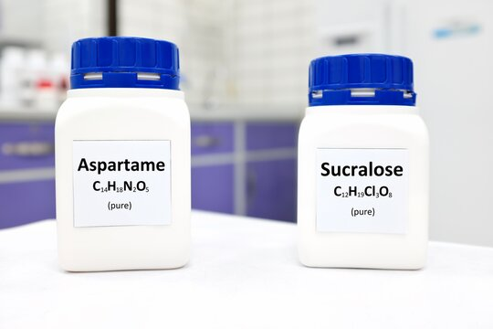 Selective focus of a bottle of pure aspartame and sucralose artificial sweetener sugar substitute chemical compound comparison. White laboratory background with copy space.