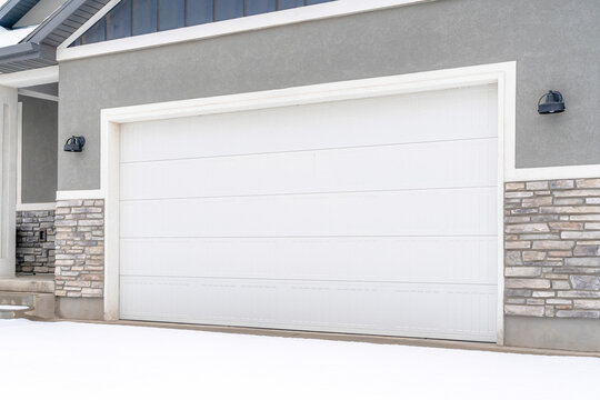Wide white garage door of home with gray exterior wall on a snowy winter day