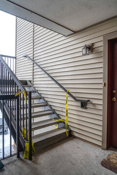 Exterior stairway of residential building with yellow caution construction tape