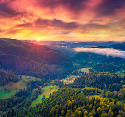 Beautiful summer scenery. Spectacular sunrise on Carpathian mountains. Fog spreads on the valley of Snidavka village, Ukraine, Europe. Majestic landscape of mountain hills glowing by sunlight.