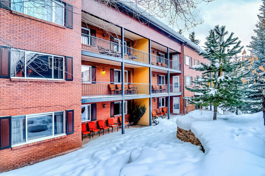 Residential building with red brick wall and balconies overlooking snowy yard