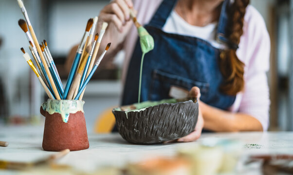 Woman mixing paint with brush inside ceramic bowl in workshop studio - Artisan work and creative craft concept