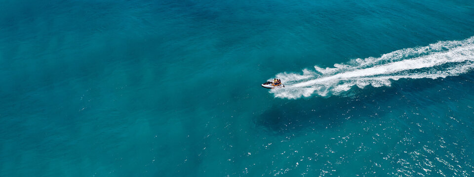 Aerial drone ultra wide photo of jet ski watercraft performing extreme manoeuvres in deep blue bay with calm sea at dusk