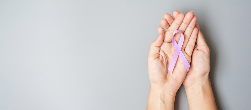 World cancer day (February 4). Woman hand hoy Lavender purple ribbon for supporting people living and illness. Healthcare and medical concept