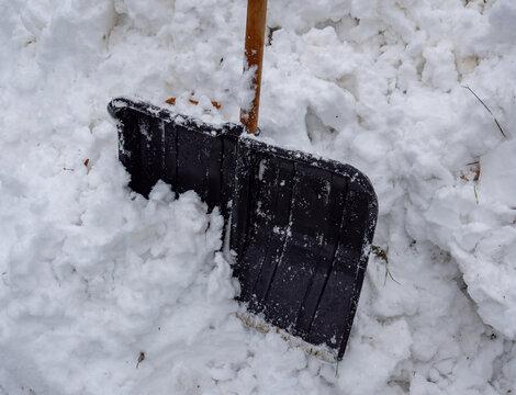 Schneeschippe in einem Schneehaufen im Winter