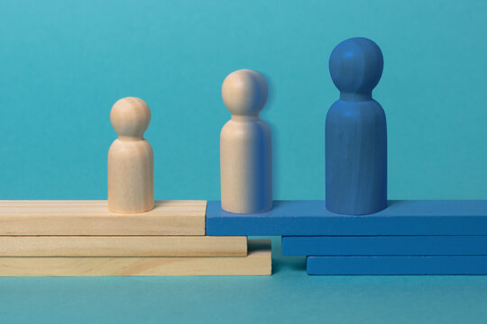 Concept of transition from child to adolescent to adult.  Wooden figures on blue background