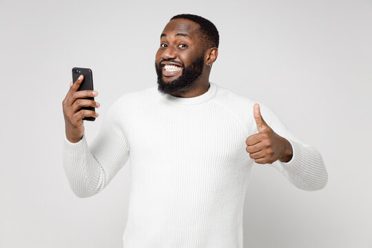 Smiling young african american man 20s wearing basic sweater standing showing thumb up using mobile cell phone typing sms message looking camera isolated on white color background studio portrait.
