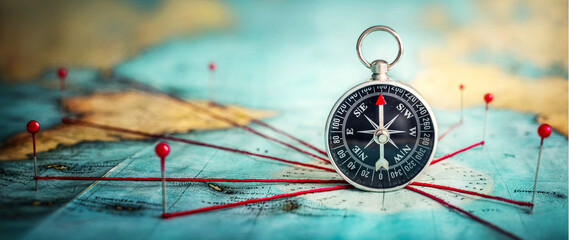 Obraz Magnetic compass  and location marking with a pin on routes on world map. Adventure, discovery, navigation, communication, logistics, geography and travel theme concept background.. Macro photo.  - fototapety do salonu