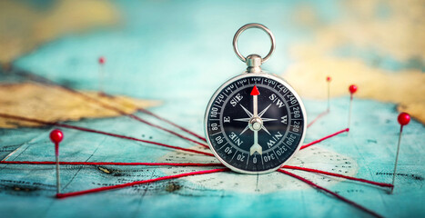 Magnetic compass  and location marking with a pin on routes on world map. Adventure, discovery, navigation, communication, logistics, geography and travel theme concept background.. Macro photo. - fototapety na wymiar