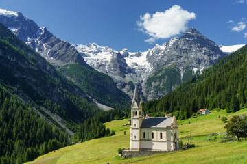 Mountain landscape along the road to Stelvio pass at summer. Church Fotobehang