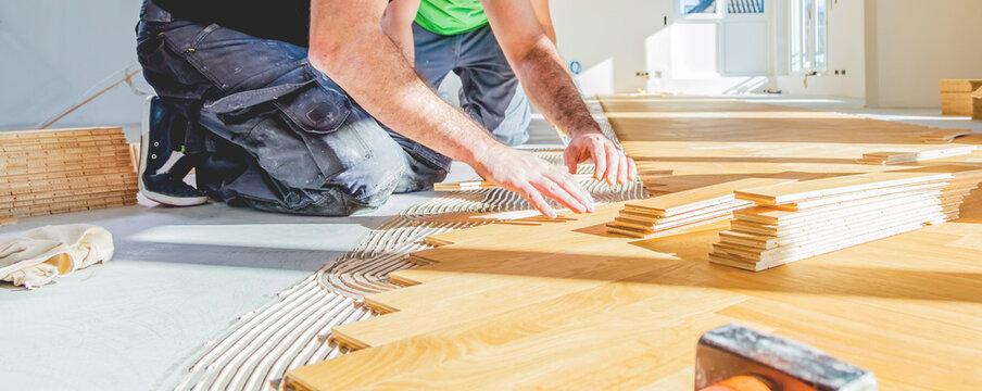 worker installing oak herringbone parquet floor during home improvement