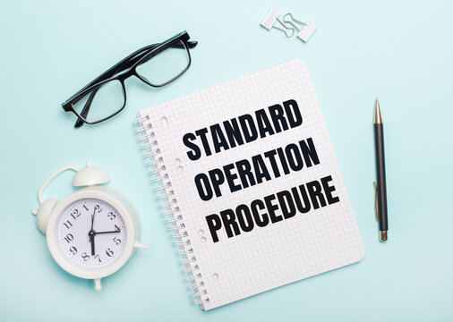 On a light blue background lie black glasses and a pen, a white alarm clock, white paper clips and a notebook with the words Standard Operating Procedure. Business concept