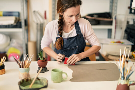 Mature woman working with clay - Art work studio handmade handcraft ceramic pottery