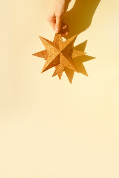 Hand holding gold star on beige background. Minimal New Year background. Space for text