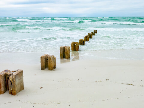 An old pier diagonally going into the waves on Siesta Key Beach with aquamarine water.