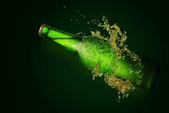 Green beer bottle with long neck in splash of beer.