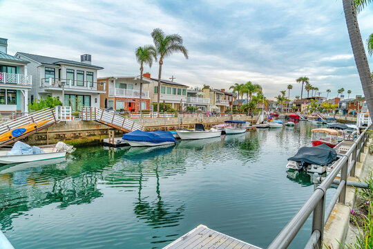 Waterfront houses with view of stairs going down boat docks at a scenic canal