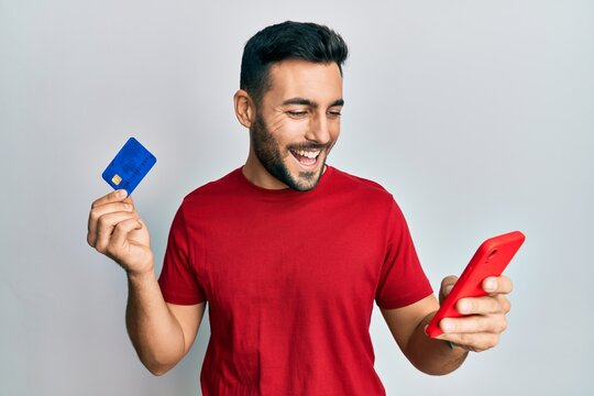 Young hispanic man holding smartphone and credit card smiling and laughing hard out loud because funny crazy joke.