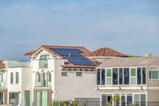 House with white exterior wall and solar panels on tile roof in Huntington Beach