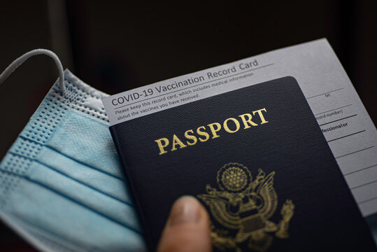 COVID-19 Vaccination Record card, Passport of USA and Medical Mask. Immune passport or certificate for travel concept.