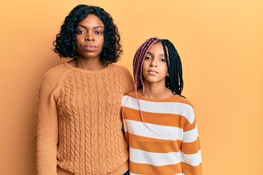 Beautiful african american mother and daughter wearing wool winter sweater relaxed with serious expression on face. simple and natural looking at the camera.