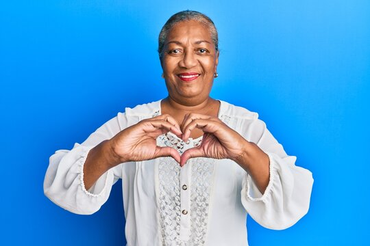 Senior african american woman wearing casual clothes smiling in love doing heart symbol shape with hands. romantic concept.