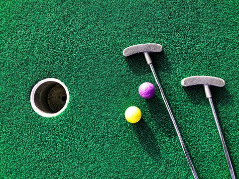 Mini golf clubs and balls on green artificial grass carpet