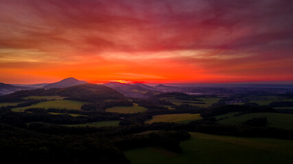 Aerial view of colorful clouds and mountainous hilly landscape at sunset over the horizon of Beskydy region.