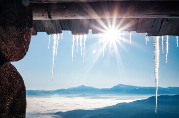 Wall Mural - Spectacular icicles shine in sun against blue sky. Splendid view with ice icicles hanging from roof.