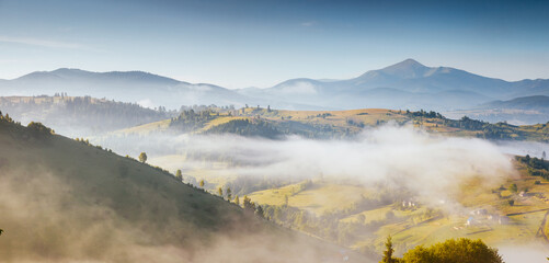 Wall Mural - Charming summer scene of a misty valley from a bird's eye view.