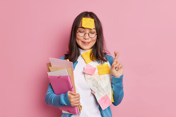 Positive schoolgirl crosses fingers believes in good luck on exam wears round spectacles stuck with...