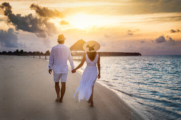 A beautiful traveler couple in white summer clothing walks along a tropical beach holding hands during sunset time Fotobehang