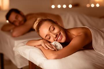 Happy Couple On Relaxing Spa Procedure Lying On Beds Indoors
