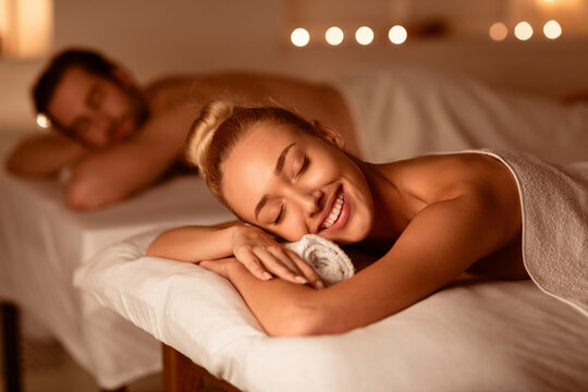 Happy Couple On Relaxing Spa Procedure Lying On Beds Indoors