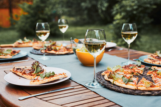 Dinner in a home garden. Pizza, salads, fruits and white wine on table in a orchard in a backyard