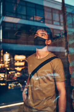 Young man standing in coffee shop at store front in the city center in the evening, wearing the face mask to avoid virus infection and to prevent the spread of disease in time of coronavirus