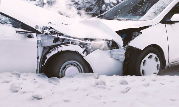 Close up view of a car crash on a snowy road in winter, where two white cars have been wrecked in a front collision